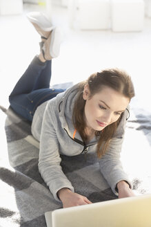Young woman lying on woollen blanket on the floor using laptop - MEMF000628