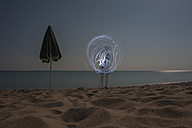 Italy, Sardinia, Tortoli, Cea beach, light painting boy with flashlight in the moonlight - JBF000224