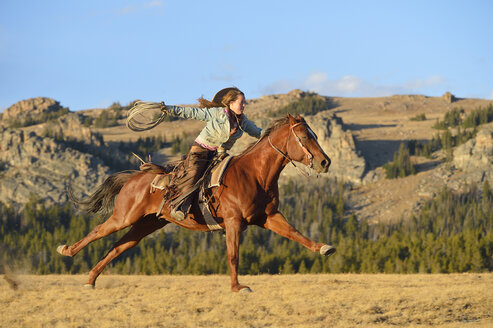 USA, Wyoming, riding cowgirl holding lasso - RUEF001391