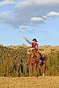 USA, Wyoming, cowboy sitting on his horse throwing lasso - RUEF001397