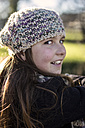 Portrait of girl wearing wool cap viewing over shoulder - MGOF000008