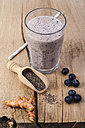 Glass of blueberry smoothie, wooden shovel of chia seeds, curcuma and blueberries on wood - ODF001005