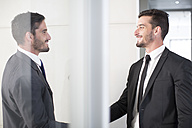 Two businessmen shaking hands in office - ZEF003131