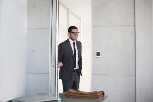 Businessman in suit opening boardroom door - ZEF003136