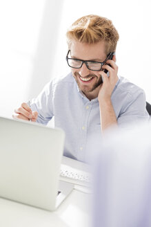Smiling young businessman on cell phone at desk - WESTF020486