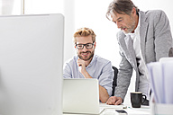 Two businessmen with laptop at desk - WESTF020489