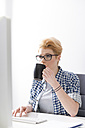 Young woman drinking coffee at desk - WESTF020510