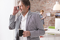 Smiling businessman on cell phone in office - WESTF020524
