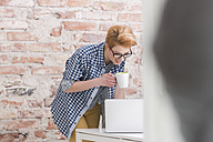 Smiling young woman with laptop and cup of coffee in office - WESTF020539