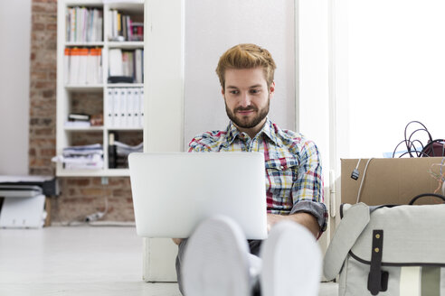 Young man sitting on floor in office using laptop next to cardboard box - WESTF020560