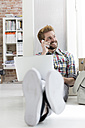Young man sitting on floor in office using laptop and cell phone - WESTF020563