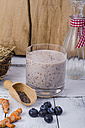 Glass of blueberry smoothie, fresh curcuma, wooden shovel of chia seeds and blueberries on wood - ODF001015