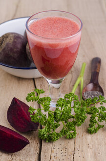 Glass of beetroot smoothie, parsley, beetroot and chia seeds on wood - ODF001027