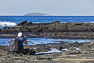 Ecuador, Galapagos Islands, Santiago, man photographing at seafront - FOF007281