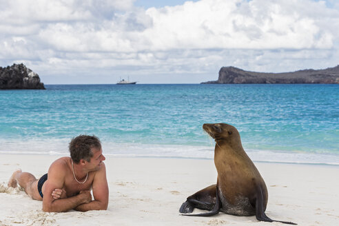 Ecuador, Galapagos Islands, Espanola, tourist and Galapagos sea lion on beach - FOF007300