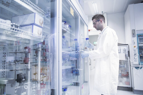 Scientist in microbiological lab opening fridge - SGF001324