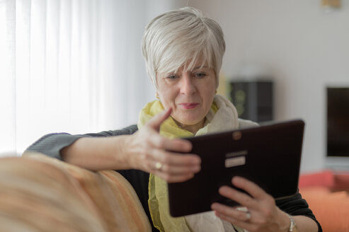 Senior woman using digital tablet on sofa - FRF000169