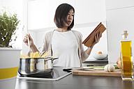 Young woman using digital tablet while cooking spaghetti - FLF000809