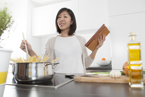 Smiling young woman holding digital tablet while cooking spaghetti - FLF000815