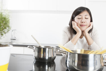 Portrait of smiling young woman relaxing while cooking - FLF000801