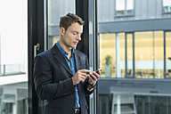 Businessman using smartphone in an office - SHKF000160