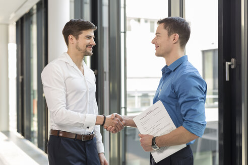 Two businessmen shaking hands in an office - SHKF000138