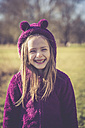 Portrait of laughing litte girl wearing purple hooded jacket - SARF001233