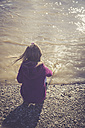 Little girl crouching at water's edge - SARF001237