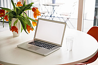 Opened laptop on a white round table with red tulips - MFF001389