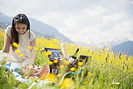 Young woman having picnic on alpine meadow - HHF005043
