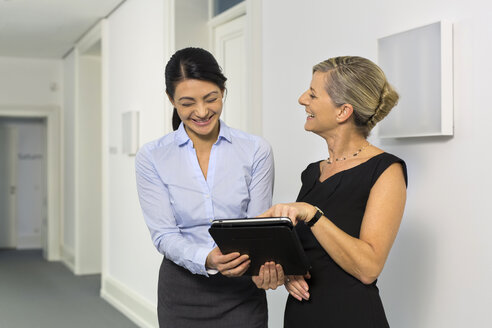 Two laughing businesswomen with digital tablet on office floor - SHKF000208