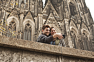 Germany, Cologne, young couple taking a picture in front of Cologne Cathedral - FEXF000238