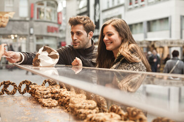 Germany, Cologne, young couple in the city at bakery - FEXF000245