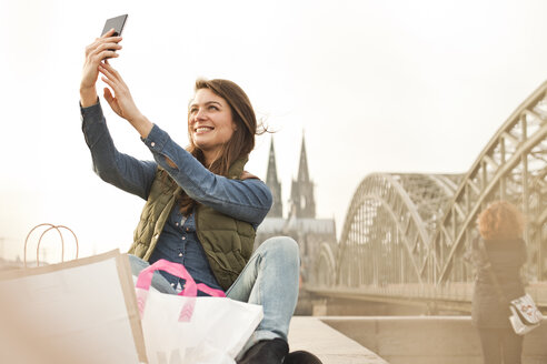 Germany, Cologne, smiling young woman with shopping bags taking a selfie - FEXF000259