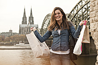 Germany, Cologne, happy young woman with shopping bags in front of Hohenzollern Bridge - FEXF000262