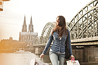Germany, Cologne, young woman with shopping bags in front of Hohenzollern Bridge - FEXF000265
