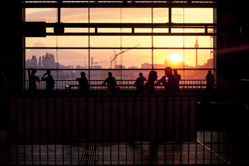 Germany, Berlin, S-Bahn station Ostkreuz, silhouettes of commuters at sunset - ZM000357