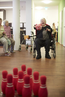 Age demented senior woman bowling with foam ball in a nursing home - DHL000506