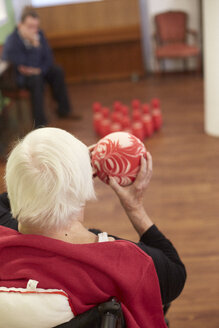 Age demented senior woman bowling with foam ball in a nursing home - DHL000514
