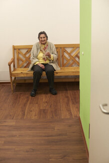 Age demented senior woman sitting on bench in a nursing home - DHL000516