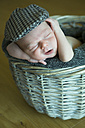 Portrait of sleeping newborn in a wickerbasket wearing cap - JTLF000032