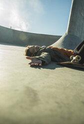 Teenage girl lying in skatepark - UUF003057