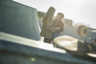 Two teenage girls in skatepark talking - UUF003059