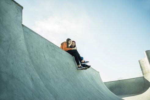 Two teenage girls in skatepark sharing cell phone - UUF003065