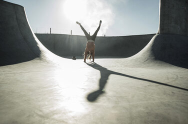 Teenage girl doing a cartwheel in skatepark - UUF003067