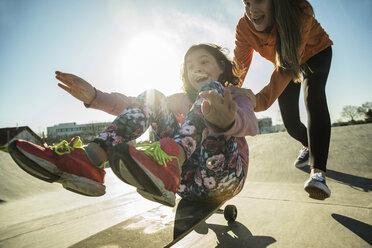 Teenage girl pushing girl on skateboard - UUF003068