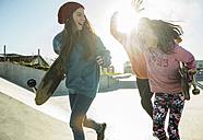 Three girls running in skatepark - UUF003077