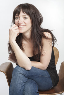 Portrait of smiling woman with dark long hair sitting on a chair - PATF000008