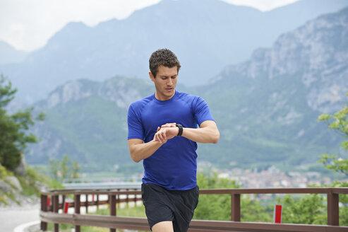 Italy, Trentino, man running on road near Lake Garda checking the time - MRF001460