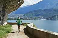 Italy, Trentino, man running at Lake Garda - MRF001473